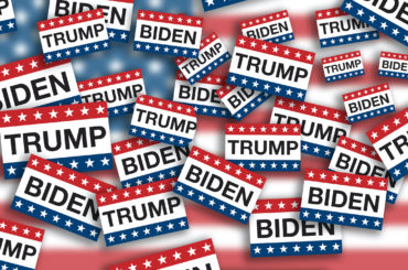 Piles of voting signs with stars and stripes from the American flag and the last names of President Donald J. Trump and Joseph R. Biden flying around on USA flag background. (Photo: AdobeStock)